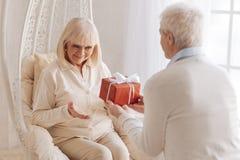 Netter mitfühlender Ehemann, der seiner Frau ein Geschenk gibt lizenzfreie stockbilder