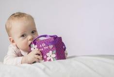 Netter 8-monatiger Junge mit einem Geschenk in einer Tasche, die auf der weißen Decke liegt und Kamera betrachtet Postkarte für M Stockbild
