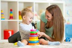 Netter Mutter- und Kinderjunge spielen zusammen Innen an Stockbild