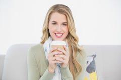 Netter netter blonder haltener Kaffee, der auf angenehmem Sofa sitzt Lizenzfreie Stockfotografie