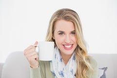 Netter netter blonder haltener Tasse Kaffee, der auf angenehmem Sofa sitzt Lizenzfreie Stockfotos