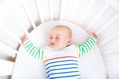 Netter neugeborener kleiner Junge, der in der runden Krippe schläft Lizenzfreie Stockbilder