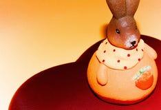 Netter Osterhase auf schönem rotem Herzen auf einem hellgelben Hintergrund Lizenzfreie Stockbilder