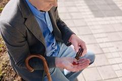 Netter Pensionär, der seine letzten Pillen auf dem Kai betrachtet Stockfotografie