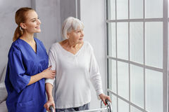 Netter Pensionär, der am Zeiteimer im Raum der Klinik geht lizenzfreies stockfoto