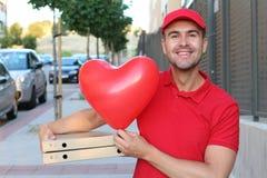 Netter Pizzalieferungskerl, der Pizzas und geformten Ballon des Herzens hält stockbilder