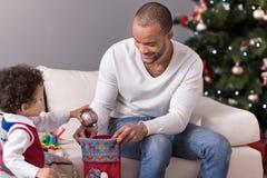 Netter positiver Junge, der eine Weihnachtsdekoration in die Socke einsetzt Lizenzfreie Stockfotografie