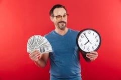 Netter positiver Mann in der bunten Sonnenbrille, die Geld und Uhr beim Blinzeln hält Lizenzfreie Stockfotografie