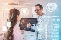 Netter Programmierer, der seiner Tochter einen modernen Griffel lächelt und zeigt Stockbilder