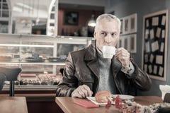 Netter reifer Mann, der geschmackvollen Kaffee während der Pause trinkt lizenzfreie stockfotografie