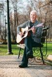 Netter reifer Mann, der Gitarrenfähigkeiten vervollkommnet stockfotografie