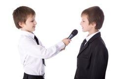 Netter Reporter des kleinen Jungen mit dem Mikrofon, das Interview isolat nimmt stockfoto