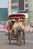 Netter Rikschafahrer mit Passagieren, Peking, China stockfotos