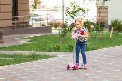 Netter Roller des kleinen Mädchens Reitim Stadtpark am hellen Sommertag Blondes Kleinkind, das Spaß auf Straße hat Aktive Freizei Stockbilder