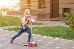 Netter Roller des kleinen Mädchens Reitim Stadtpark am hellen Sommertag Blondes Kleinkind, das Spaß auf Straße hat Aktive Freizei Lizenzfreies Stockfoto