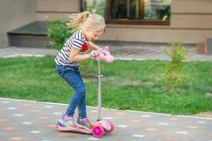 Netter Roller des kleinen Mädchens Reitim Stadtpark am hellen Sommertag Blondes Kleinkind, das Spaß auf Straße hat Aktive Freizei Lizenzfreie Stockfotos