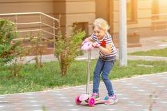 Netter Roller des kleinen Mädchens Reitim Stadtpark am hellen Sommertag Blondes Kleinkind, das Spaß auf Straße hat Aktive Freizei Stockbild