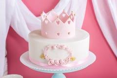 Netter rosa Kuchen mit einer Krone auf dem Tisch zum Geburtstag für eine Prinzessin Lizenzfreies Stockbild