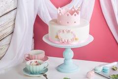 Netter rosa Kuchen mit einer Krone auf dem Tisch zum Geburtstag für eine Prinzessin Lizenzfreie Stockfotos