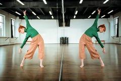 Netter rothaariger Tanzlehrer in einem grünen Rollkragen, der Neigungen tut stockbilder