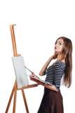 Netter schöner Mädchenkünstler, der ein Bild auf Segeltuchgestell malt Raum für Text Weißer Hintergrund des Studios, lokalisiert Stockfotografie