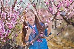 Netter schöner stilvoller gekleideter Brunette und blonde Mädchenschwestern, die auf einem Feld des jungen Pfirsichbaums des Früh Stockbilder