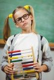 Netter Schüler, der Abakus in einem Klassenzimmer hält Stockfoto
