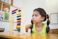 Netter Schüler, der Abakus im Klassenzimmer verwendet Stockfoto