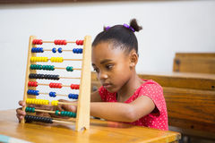 Netter Schüler, der Abakus im Klassenzimmer verwendet Lizenzfreie Stockfotos