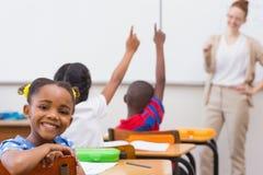 Netter Schüler, der an der Kamera im Klassenzimmer lächelt Lizenzfreies Stockfoto