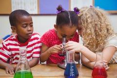 Netter Schüler, der durch Mikroskop schaut Stockfoto
