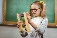 Netter Schüler, der mit Abakus in einem Klassenzimmer berechnet Lizenzfreies Stockfoto