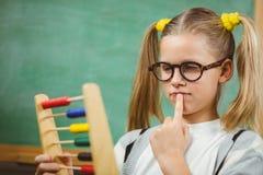 Netter Schüler, der mit Abakus in einem Klassenzimmer berechnet Lizenzfreie Stockfotografie