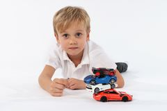 Netter schauender Junge, der mit einem Stapel von Autospielwaren liegt und eine aufrichtige neutrale Person und einen stolzen Bli stockfotografie