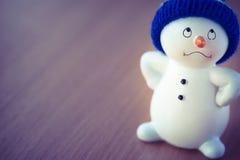 Netter Schneemann auf Holztisch Stockbild