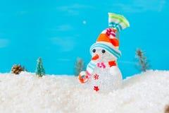 Netter Schneemann im Schnee über blauem hölzernem Hintergrund Stockfotografie