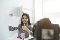 Netter Schuss des attraktiven Mädchens sitzend vor Kamera und ein leeres Papier ohne Wörter auf dem zeigend Sie stellt dar stockbilder