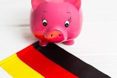 Netter Schweingeldkasten und Deutschland-Flagge - sparen Sie Geld in Deutschland-Konzept Closedup stockfotografie