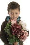 Netter sechs Einjahresjunge mit Blumen Stockfoto