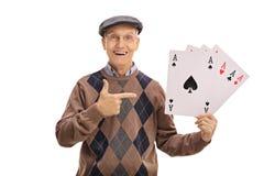 Netter Senior, der vier Asse und Zeigen hält Lizenzfreies Stockbild
