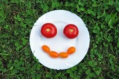 Netter smiley von der frischen Tomate auf einer weißen Platte im Gras Stockfoto