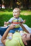 Netter Sohn und sein Vater auf Gras Stockfoto