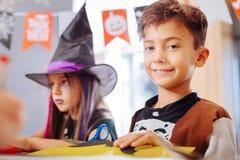 Netter sorgfältiger dunkelhaariger Junge, der mit anderen Kindern im Kindergarten spielt lizenzfreie stockbilder