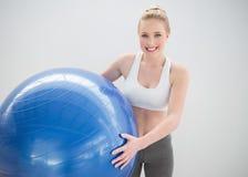 Netter sportlicher blonder haltener Übungsball Stockbilder