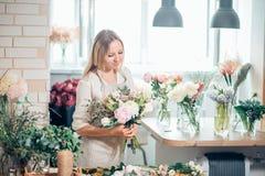Netter starker junger weiblicher Florist in der Glasfunktion im Blumenladen Stockbilder