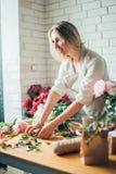 Netter starker junger weiblicher Florist in der Glasfunktion im Blumenladen Lizenzfreies Stockfoto