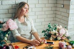 Netter starker junger weiblicher Florist in der Glasfunktion im Blumenladen Stockfoto