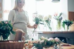 Netter starker junger weiblicher Florist in der Glasfunktion im Blumenladen Lizenzfreie Stockfotos