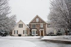Netter Stein stellte Haus im Schnee gegenüber Stockbild