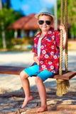 Netter stilvoller Junge auf Schwingen auf dem Strand stockfoto
